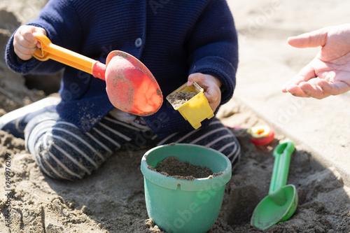Obraz na plátně  砂場で砂遊びする子供