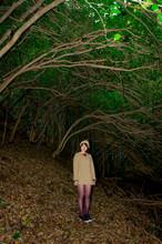 落葉の中に立つ女性