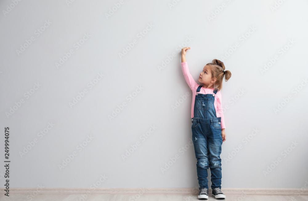 Fototapeta Portrait of cute little girl near light wall