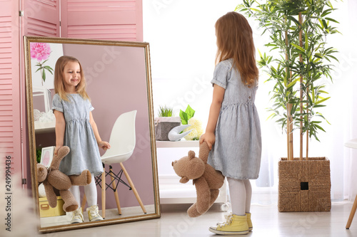 Obraz Cute little girl with teddy bear looking in mirror at home - fototapety do salonu