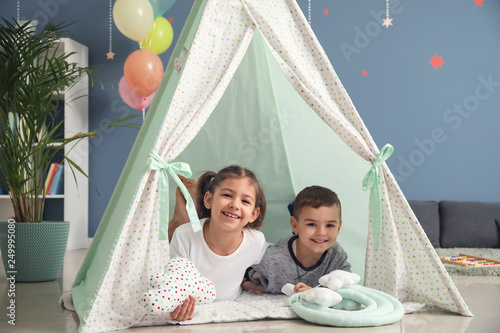 Cute little children lying in hovel at home Canvas