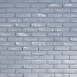 part of white grey brick wall with spots of sunlight