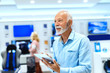Close up of smiling bearded old man holding tablet and looking up while standing in tech store.
