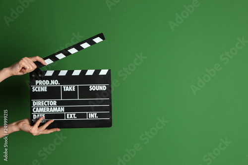 Stampa su Tela Female hands with cinema clapperboard on color background