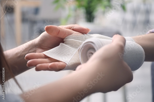 Billede på lærred Woman applying bandage onto female wrist, closeup