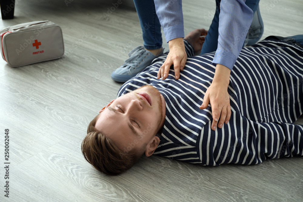 Fototapety, obrazy: Woman providing first aid to her unconscious husband at home