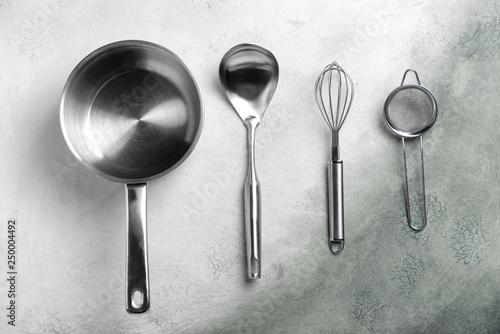 Fotografía  Stainless steel kitchen utensils on grey background