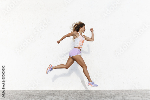 Poster Jogging Strong athletic happy sportswoman wearing sport shorts jump across white concrete wall facing forward running in air, smiling accomplished, setting goal, workout, jogging, sprint along quay