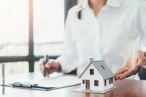 Valokuvatapetti House model with real estate agent and customer discussing for contract to buy house, insurance or loan real estate background