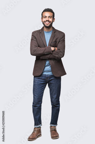 Full length studio portrait of handsome smiling young man isolated on gray background Wall mural