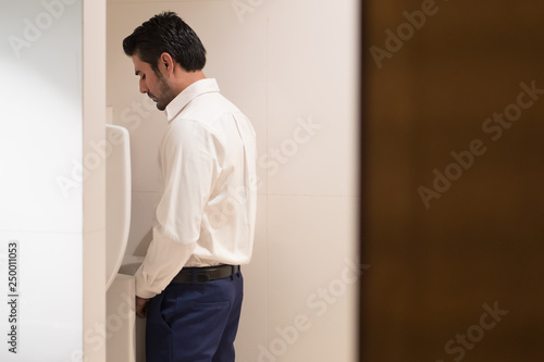 Fotografía Asian man urinating in toilet; portrait of Indian man using water closet, WC for
