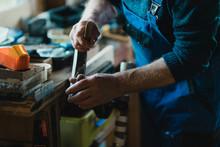 Senior Using Surform Tool On Wood
