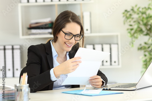 Photo Happy office worker reading a letter