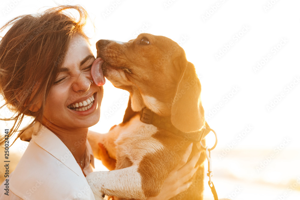 Fototapety, obrazy: Image of happy woman 20s hugging her dog, while sitting on sand by seaside