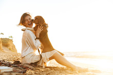 Image Of Cheerful Woman 20s Hugging Her Dog, While Sitting On Sand By Seaside