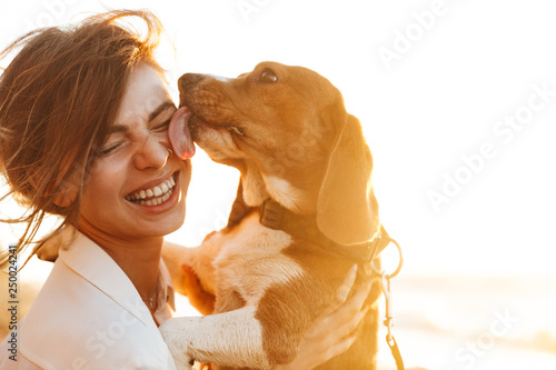 Image of happy woman 20s hugging her dog, while sitting on sand by seaside Canvas Print