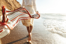 Portrait Of Positive Girl 20s Walking With Waving Scarf, Along Seashore