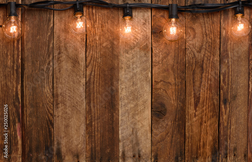 Fotografía  Vintage garland string lights on old wooden wall border with copy space