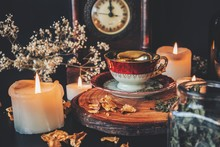 Making A Cup Of Tea In Witch's Kitchen. A Vintage Red White And Gold Colored Teacup Placed On A Wooden Platform On A Black Table. Kitchen Witchcraft With Tea, Herbs And Spices With Burning Candles