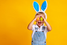 Funny Happy Child Boy With Easter Eggs And Bunny Ears On Yellow.
