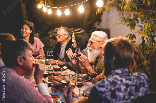 Pinturas sobre lienzo  Happy family eating and drinking wine at barbecue dinner outdoor - Focus on tatt