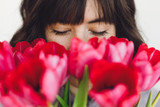 Fototapeta Tulipany - Beautiful brunette girl portrait with red tulips closeup on white background indoors, space for text. Stylish young woman  smelling tulips with closed eyes. Fresh aroma scent concept