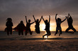silhouette of women jumping at sunset on the beach