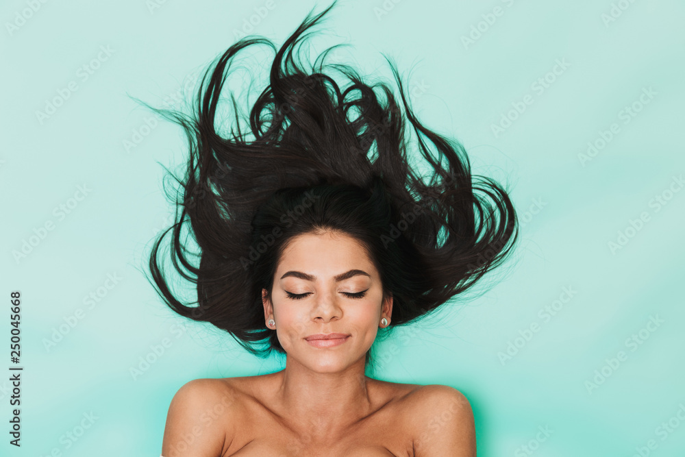 Fototapety, obrazy: Beautiful young woman lies isolated on blue light background. Healthy hair concept.