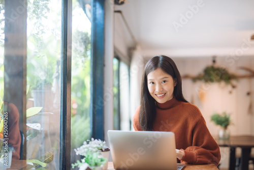 Fototapety, obrazy: Happy young Asian girl working at a coffee shop with a laptop looking at camera.