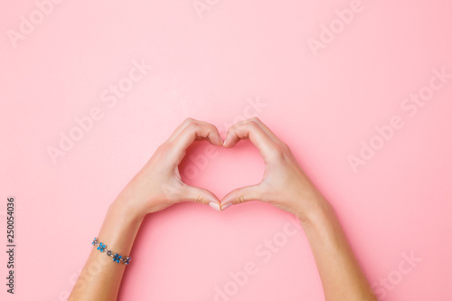 Obraz Heart shape created from young woman's hands on pastel pink background. Love and happiness concept. Empty place for emotional, sentimental text, quote or sayings. Closeup. Top view. - fototapety do salonu
