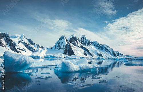 Wall Murals Blue jeans Blue Ice covered mountains in south polar ocean. Winter Antarctic landscape. The mount's reflection in the crystal clear water. The cloudy sky over the massive rock glacier. Travel wild nature