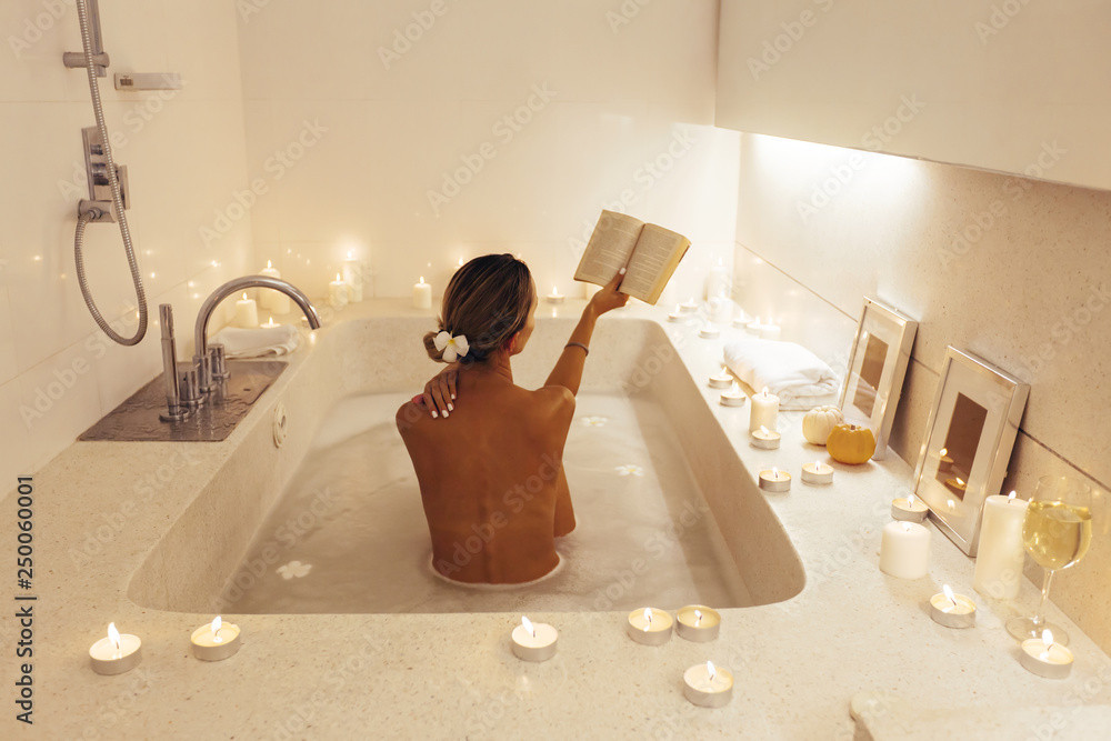 Fototapeta Woman relaxing in bath with candles
