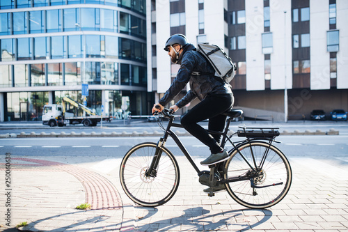 Male courier with bicycle delivering packages in city Fototapeta