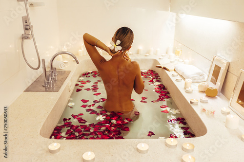 Photo Woman relaxing in bath with flower petals