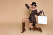 Fashion Model girl full length portrait isolated on beige background. Beauty stylish blonde woman posing in fashionable clothes in studio. Casual style, beauty accessories,hat and handbag