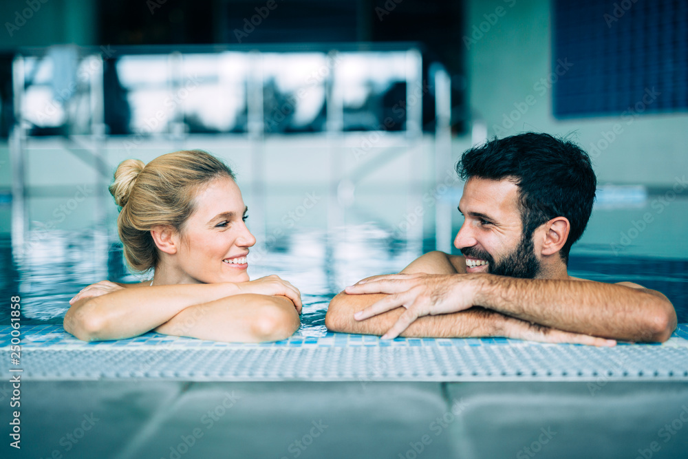 Fototapeta Happy attractive couple relaxing in swimming pool