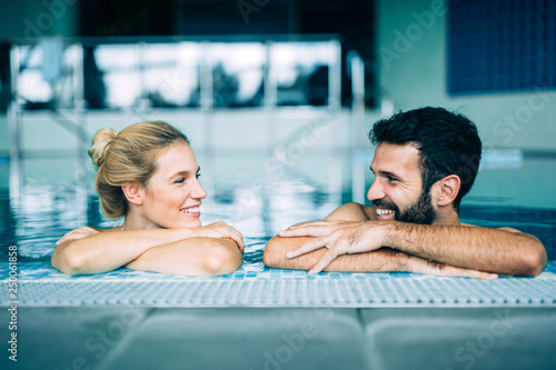 Obraz Happy attractive couple relaxing in swimming pool - fototapety do salonu