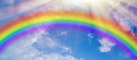 Colorful rainbow and sun rays on blue cloudy sky