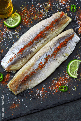 Herring fillet with sea salt and spices on a gray stone board.