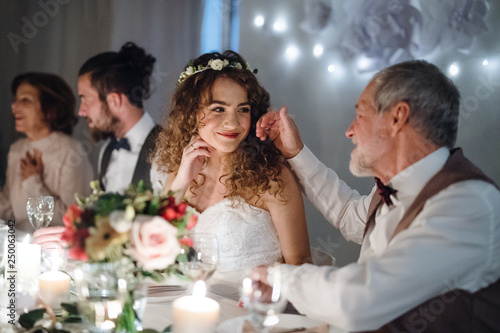 Photo A loving father and beautiful bride sitting at the table on a wedding, talking