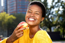 Healthy Young Woman Eating Apple Outdoors