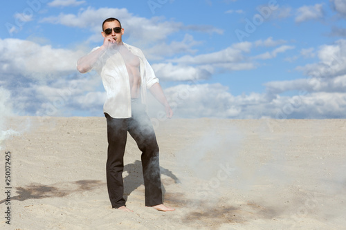 Fotografie, Obraz  Young macho man in glasses stands amid the smoke in the desert and smokes a cigar