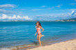Happy young woman in pink swimsuit with long hair jumping on the tropical beach near the blue sea while sky is blue, Koh Samui, Thailand