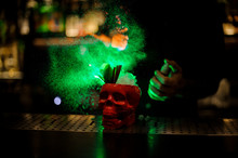 Bartender Spraying On The Delicious Cocktail In The Scull Cup From The Vaporizer In The Green Light