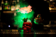 Bartender Spraying On The Cocktail In The Scull Red Cup From The Vaporizer In The Green Light