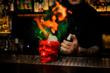 Bartender Spraying On The Delicious Cocktail In The Scull Cup From The Vaporizer And Flame It