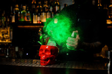 Bartender Spraying On The Delicious Cocktail In The Scull Cup From The Vaporizer