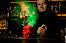 Bartender Spraying On The Cocktail In The Red Scull Cup From The Vaporizer And Flame It