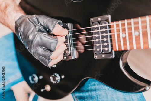 Fototapety, obrazy: Closeup of rocker hand in leather glove playing rock on electric guitar
