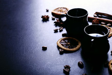 A Cup Of Coffee, Star Anise, Cinnamon, Dried Orange And Coffee Beans On A Dark Kitchen Countertop. Fragrant Spices For A Drink, Close-up, Top View, Flat Ley.